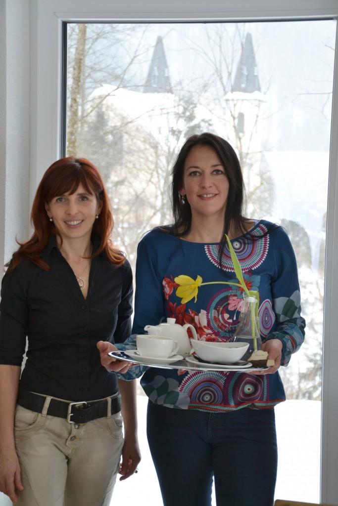 Petra Gassner (l.) und Ulrike Ginzler führen das Fasten- und Pilgerhaus Maria Seesal (im Hintergrund die Wallfahrtskirche). Foto: eisenstrasse.info