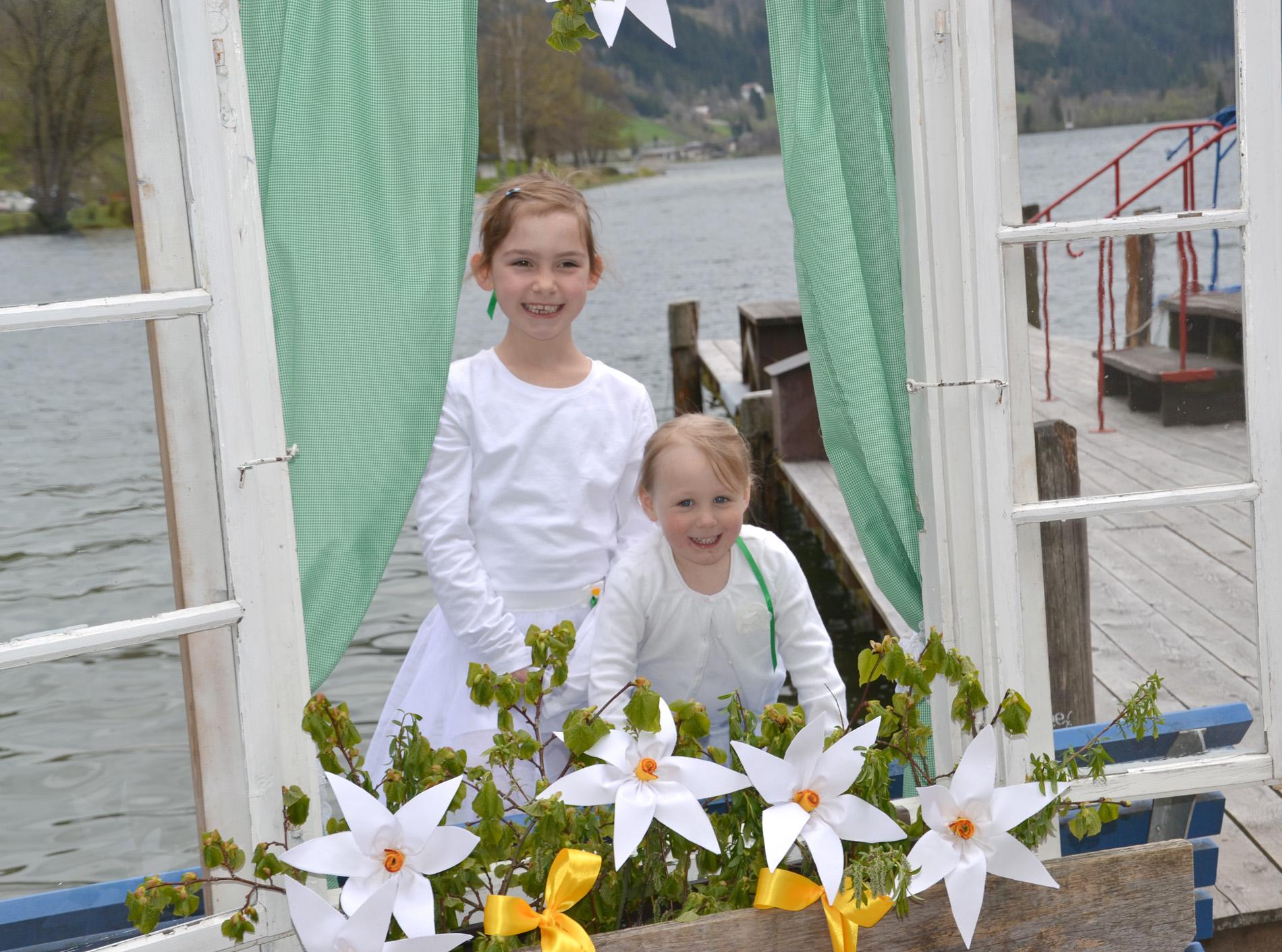 Flora Aigner und Miriam Mayr strahlen durch ein Narzissen-Fotofenster. Die Fenster werden heuer an mehreren Standorten aufgestellt. Foto: eisenstrasse.info